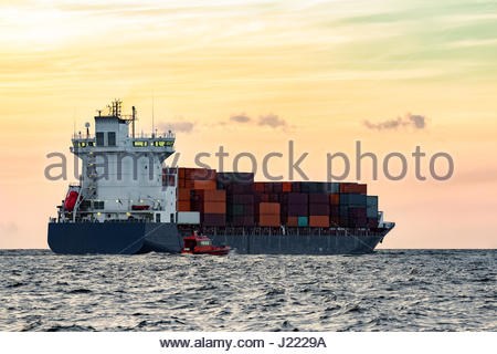 Blue container ship leaving Riga and entering Baltic sea - Stock Photo