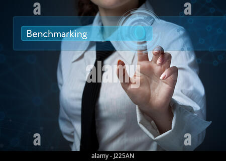Business, technology, internet and networking concept. Business woman presses a button on the virtual screen: Benchmarking - Stock Photo