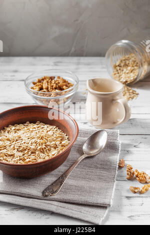 Oat flakes in brown clay bowl ready to cook, scattered oat flakes, walnuts, jug with milk and spoon on the light - Stock Photo