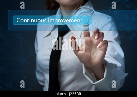 Business, technology, internet and networking concept. Business woman presses a button on the virtual screen: Continuous - Stock Photo