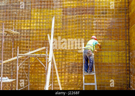 Construction worker is binding rebar for tall reinforced concrete construction at the building site. - Stock Photo
