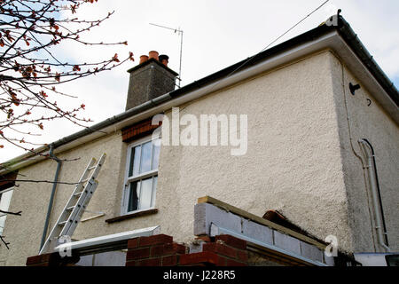 Refurbishment work in progress on a semi-detached house with rendered frontage and part-built porch. A ladder leans - Stock Photo