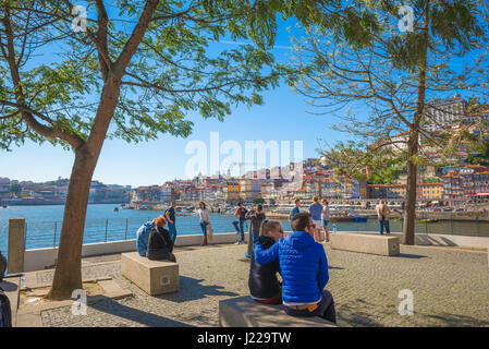 Porto Portugal Gaia, from a terrace on the Gaia side of the Douro River tourists relax and look across to the historic - Stock Photo