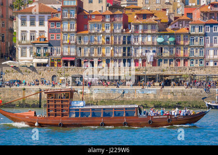 Porto Portugal Ribeira, on the Douro River a cruise boat carrying tourists sails past historic buildings sited along - Stock Photo