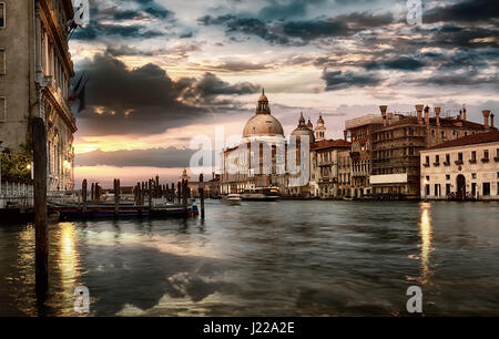 Dramatic sky over Grand Canal and Basilica di Santa Maria della Salute in Venice at sunset, Italy - Stock Photo