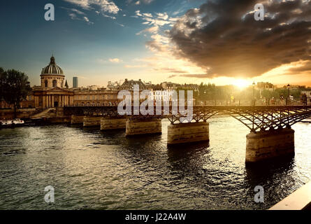 View on Pont des Arts and Institut de France in Paris at sunset - Stock Photo