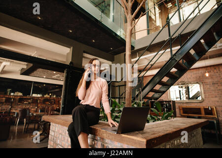 Creative young woman sitting in office cafeteria with laptop and talking on mobile phone. Female executive working - Stock Photo