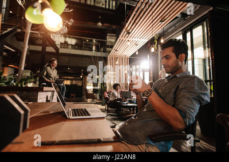 Handsome young man sitting at office cafe and using mobile phone. Casual businessman reading text message on his - Stock Photo