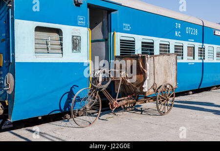 Battered, worn out tricycle next to a railway carriage at Kathgodam Station, Nainital District, Uttarakand, northern - Stock Photo