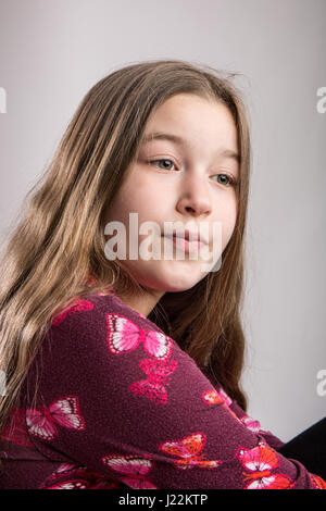 Portrait of an eleven year old girl looking thoughtful - Stock Photo