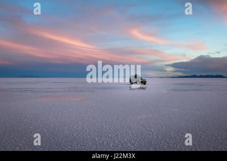 Off-road vehicle at sunrise in Salar de Uyuni salt flat - Potosi Department, Bolivia - Stock Photo