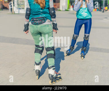 Two girls rollers meet each other in the park - Stock Photo