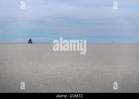 Cars disappearing into horizon in Salar de Uyuni salt flat - Potosi Department, Bolivia - Stock Photo