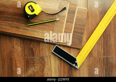 Laminate floor planks and tools on wooden background. Top view. - Stock Photo