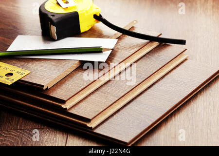 Laminate floor planks and tools on wooden background - Stock Photo