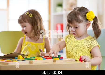 Preschool children playing with educational sorter toys in classroom, kindergarten or home - Stock Photo