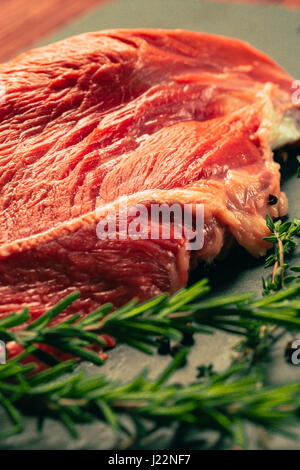 raw beef meat with spices on slate stone kitchen board - Stock Photo