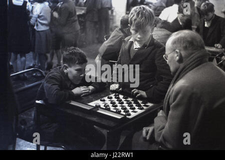 1950s, an eager young lad sitting at a small table playing a game of draughts against a man, with a friend in support, - Stock Photo
