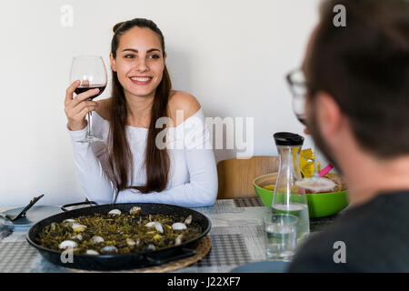 Portrait of smiling woman with glass of red wine sitting at laid table looking at her boyfriend - Stock Photo
