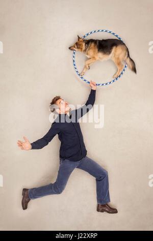 Man training his dog to jump through a hoop - Stock Photo