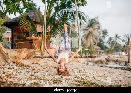 Woman having fun on a swing at the beach - Stock Photo