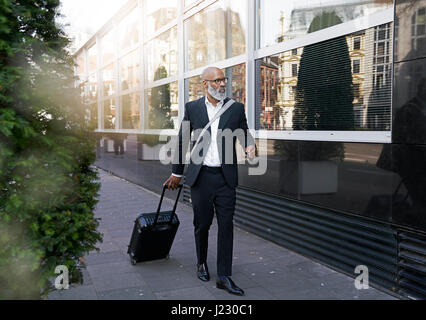 Mature businessman walking in street, pulling trolley bag - Stock Photo