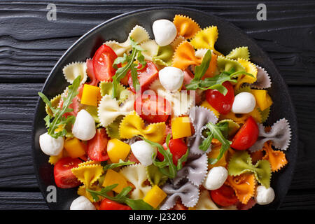 Italian food: farfalle pasta with vegetables and mozzarella close-up on a plate. horizontal view from above - Stock Photo