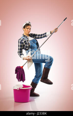 Cheerful woman with mop and bucket ready to clean the floor on pink background - Stock Photo