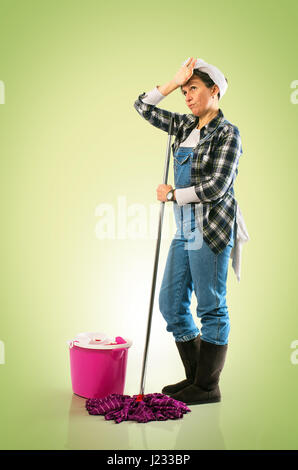 Woman with mop and bucket tired of cleaning the floor on green background - Stock Photo