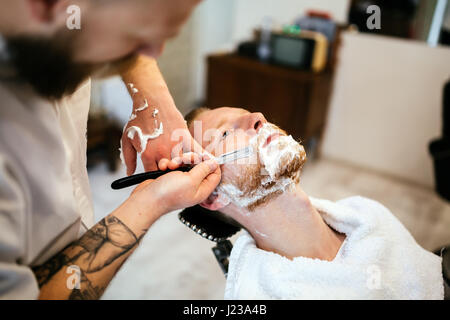 Retro shaving with foam in barber shop - Stock Photo