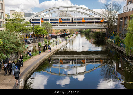 Overground train crossing the Regent's Canal at Haggerston with people walking along footpath in a stretch of the - Stock Photo