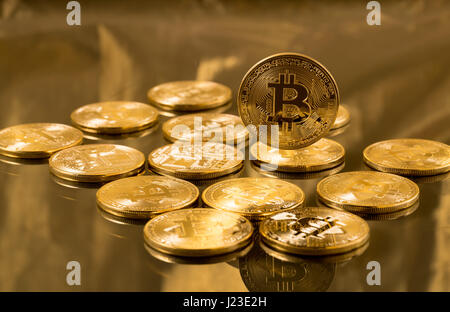 Stack of bitcoins on gold background - cyber currency and cryptocurrency vitual tokens - Stock Photo