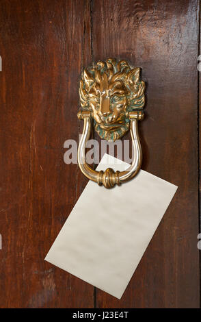 Blank Envelope with space for text placed under a brass lion head door knocker on old oak door