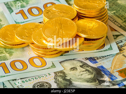 Stack of American gold eagle gold bullion coins on new design of US currency 100 dollar bills - Stock Photo