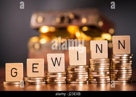 Stack of coins and the word profit in front of a treasure chest. - Stock Photo