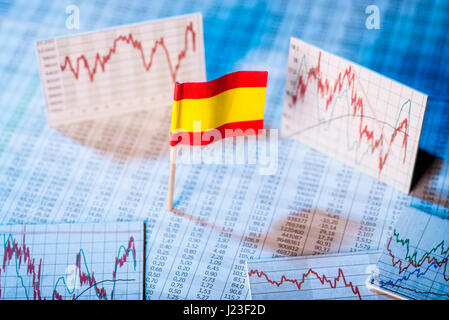 Spanish flag with rate tables and graphs for economic development. - Stock Photo