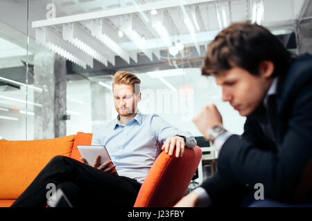 Business people looking at their devices and working - Stock Photo