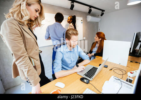 Business people collaborate in office and work on computer - Stock Photo