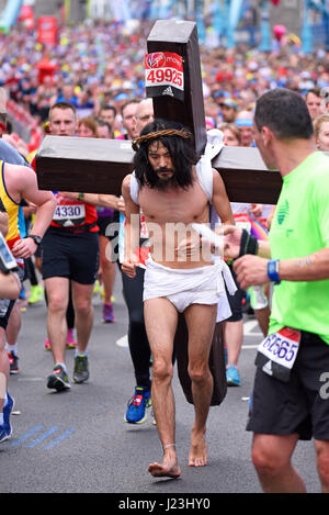 Makoto Takeuchi as Christ at the 2017 Virgin London Marathon after crossing Tower Bridge and alongside the Tower - Stock Photo
