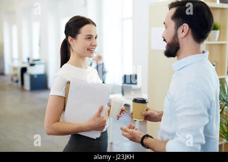 Portrait of smiling young woman talking to colleague during break in office, both holding paper coffee cups - Stock Photo