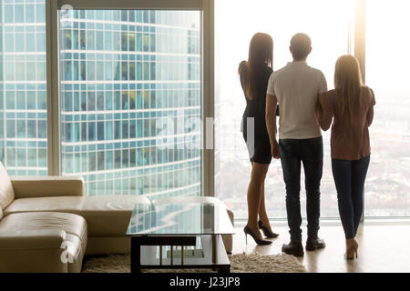 Man and two women looking out the window, rear view - Stock Photo