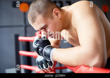 Side view portrait of sweaty exhausted shirtless boxer resting, catching breath after hard fight in boxing ring - Stock Photo