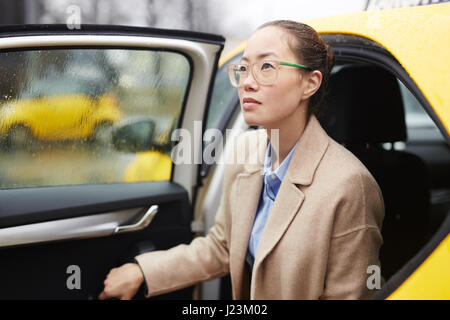 Modern woman in stylish clothes getting out of car - Stock Photo