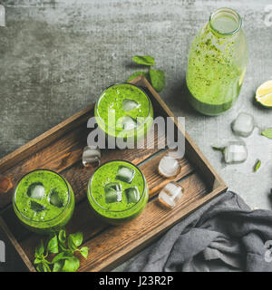 Fresh smoothie with ice cubes, mint, lime over grey background - Stock Photo