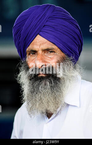 Pathankot, India, september 9, 2010: Face of indian old sikh in violet turban with beard. - Stock Photo