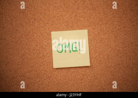 Close up shot of a note reading OMG stuck on a cork board. - Stock Photo