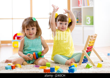 Little kids play with abacus and constructor toys, early learning - Stock Photo