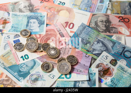 New British £1 & £2 Coins on a background of Euros and £5 pound notes - Stock Photo