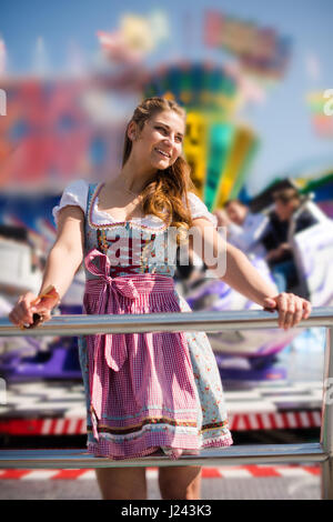 Attractive young woman at German funfair Oktoberfest with traditional dirndl dress and joyride in the background - Stock Photo
