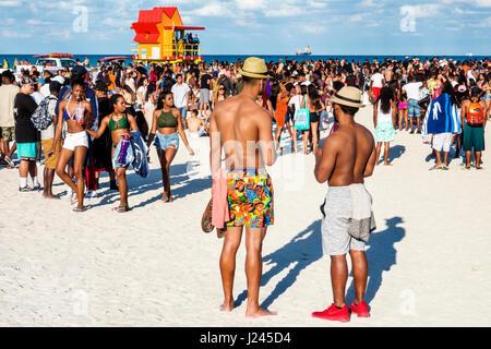 Miami Beach Florida Spring Break lifeguard tower Black man woman teen boy girl crowd young adult college student - Stock Photo